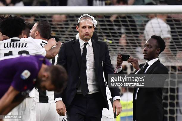 Juventus' Italian coach Massimiliano Allegri his head covered in foam reacts as Juventus players celebrate after securing the club's 8th consecutive...
