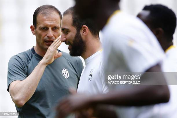 Juventus' Italian coach Massimiliano Allegri talks to Juventus' forward Gonzalo Higuain from Argentina as he attends the training session during the...
