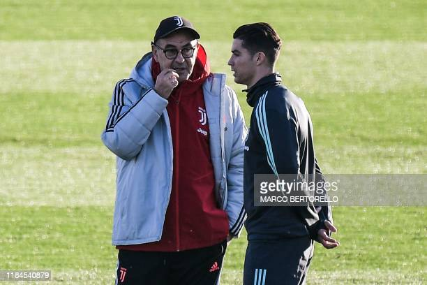 Juventus' Italian coach Maurizio Sarri talks to Juventus' Portuguese forward Cristiano Ronaldo on November 25, 2019 during a training session at the...