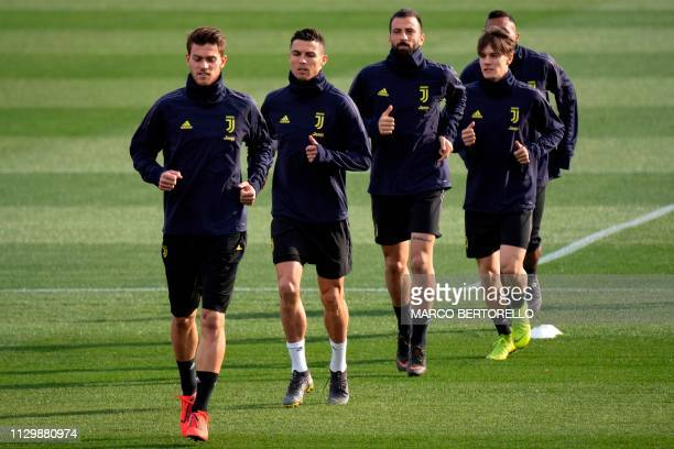 Juventus' Italian defender Daniele Rugani and Juventus' Portuguese forward Cristiano Ronaldo run next to teammates during a training session on the...