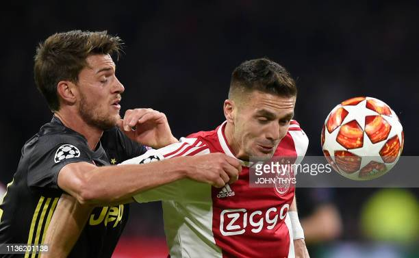 Juventus' Italian defender Daniele Rugani vies for the ball with Ajax's Serbian forward Dusan Tadic during the UEFA Champions League first leg...