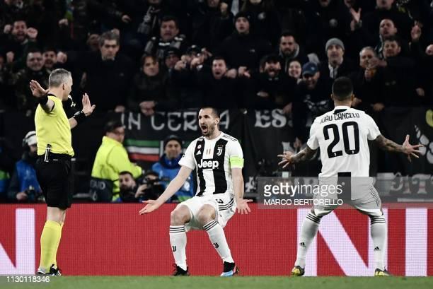 Juventus' Italian defender Giorgio Chiellini and Juventus' Portuguese defender Joao Cancelo contest Dutch referee Bjoern Kuipers decision to not...