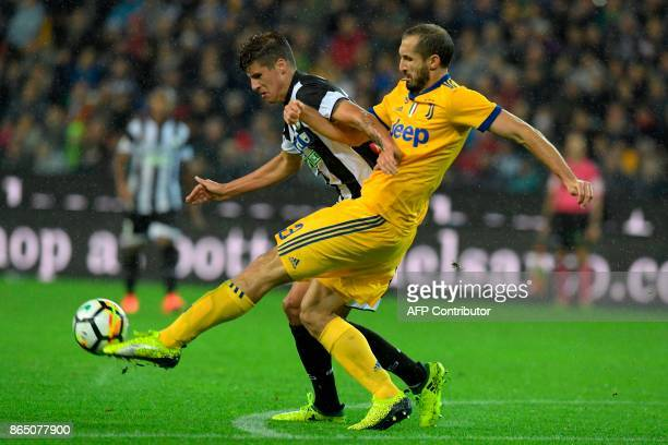 Juventus' Italian defender Giorgio Chiellini fights for the ball with Udinese's Croatian forward Stipe Perica during the Italian Serie A football...
