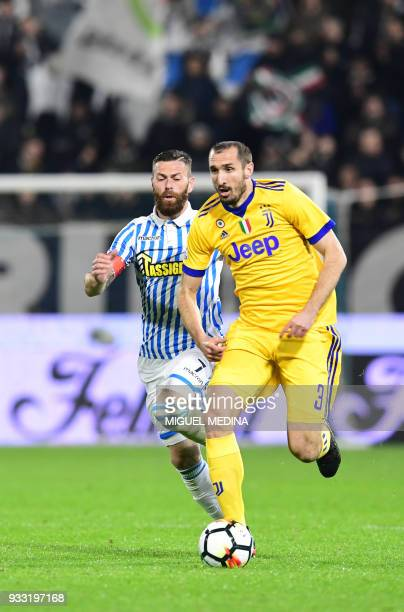 Juventus' Italian defender Giorgio Chiellini vies with Spal's captain Italian forward Mirco Antenucci during the Italian Serie A football match Spal...
