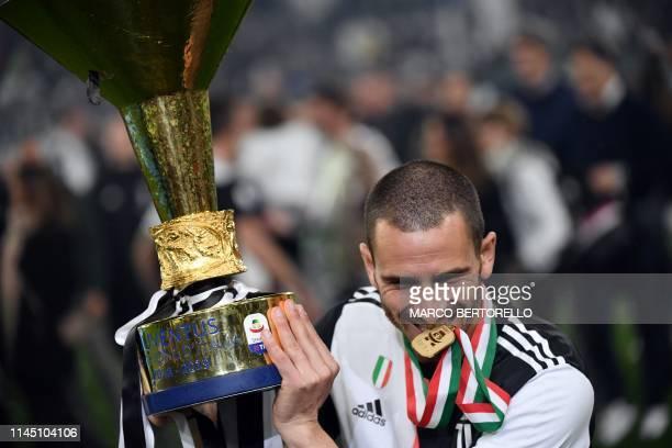 Juventus' Italian defender Leonardo Bonucci celebrates with the Italian Champion's trophy at the end of the Italian Serie A football match Juventus...
