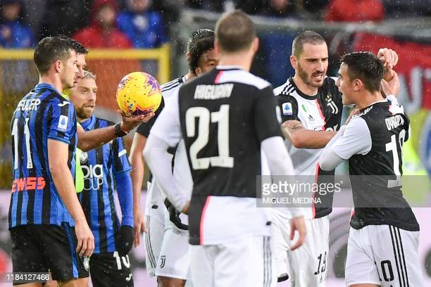 Juventus' Italian defender Leonardo Bonucci holds off Juventus' Argentine forward Paulo Dybala , arguing during the Italian Serie A football match...
