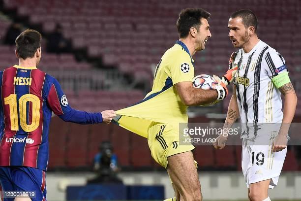 Juventus' Italian defender Leonardo Bonucci reacts as Barcelona's Argentinian forward Lionel Messi pulls on the jersey of Juventus' Italian...