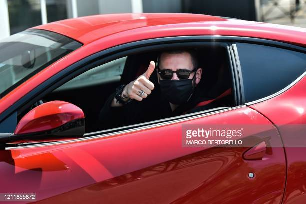 Juventus' Italian defender Leonardo Bonucci, wearing a face mask, gestures as he arrives in his car at the Juventus' Continassa training ground in...