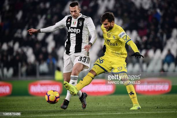 Juventus' Italian forward Federico Bernardeschi and Chievo's Finnish midfielder Perparim Hetemaj go for the ball during the Italian Serie A football...