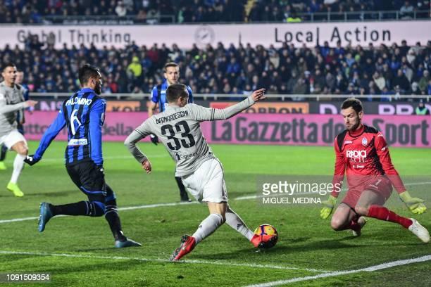 Juventus' Italian forward Federico Bernardeschi challenges Atalanta's Albanian goalkeeper Etrit Berisha during the Italian Tim Cup round of eight...