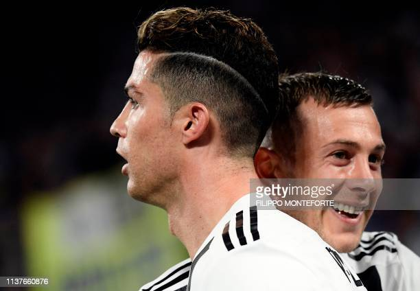 Juventus' Italian forward Federico Bernardeschi reacts next to Juventus' Portuguese forward Cristiano Ronaldo while waiting for the VAR decision...