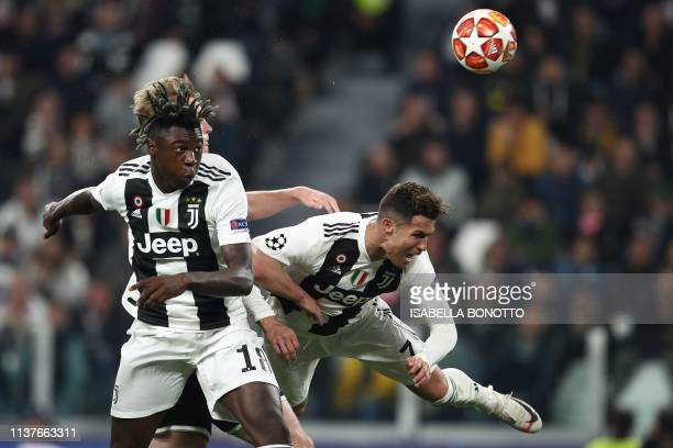 TOPSHOT Juventus' Italian forward Moise Kean and Juventus' Portuguese forward Cristiano Ronaldo go for a header during the UEFA Champions League...