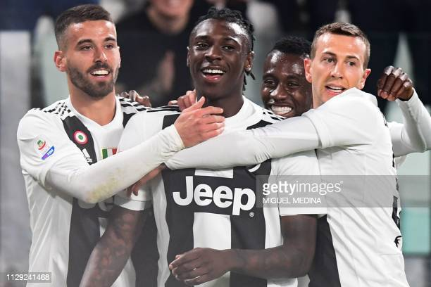 Juventus' Italian forward Moise Kean celebrates opening the scoring with Juventus' Italian defender Leonardo Spinazzola Juventus' French midfielder...