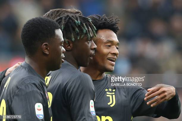 Juventus' Italian forward Moise Kean celebrates with Juventus' Italian defender Paolo Gozzi Iweru and Juventus' Colombian midfielder Juan Cuadrado...