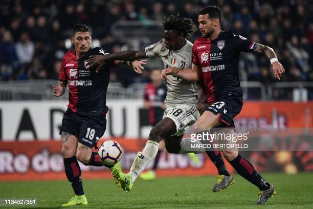 Juventus' Italian forward Moise Kean challenges Cagliari's Italian defender Fabio Pisacane and Cagliari's Italian defender Luca Ceppitelli during the...
