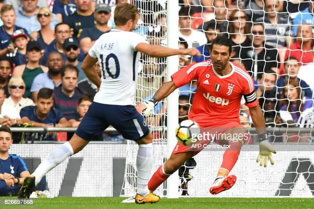 Juventus' Italian goalkeeper Gianluigi Buffon comes out to attemt a save as Tottenham Hotspur's English striker Harry Kane threatens during the...