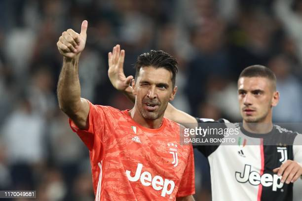 Juventus' Italian goalkeeper Gianluigi Buffon reacts next to Juventus' Turkish defender Merih Demiral at the end of the Italian Serie A football...