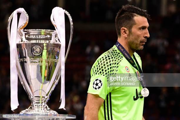 Juventus' Italian goalkeeper Gianluigi Buffon walks past the trophy after Real Madrid won the UEFA Champions League final football match between...