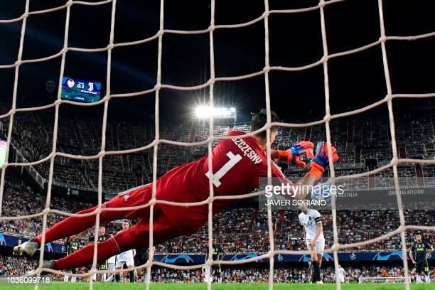 Juventus' Italian goalkeeper Wojciech Szczesny stops a penalty kicked by Valencia's Spanish midfielder Daniel Parejo during the UEFA Champions League...