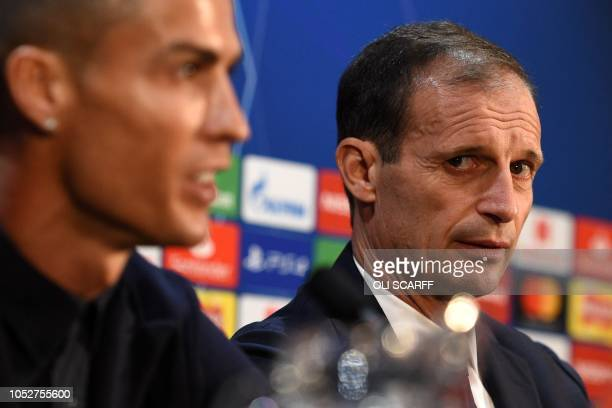 TOPSHOT Juventus' manager Massimiliano Allegri looks over as Juventus' Portuguese striker Cristiano Ronaldo answers a question during a press...