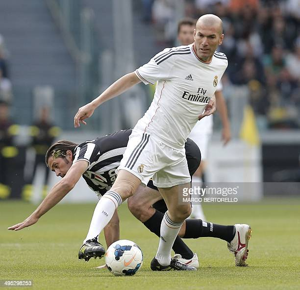 Juventus' midfielder Alessio Tacchinardi fights for the ball with Real Madrid's midfielder Zinedine Zidane during the Unesco Cup football match...