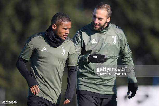 Juventus' midfielder Douglas Costa from Brazil and Juventus' forward Gonzalo Higuain from Argentina take part in a training session on the eve of the...