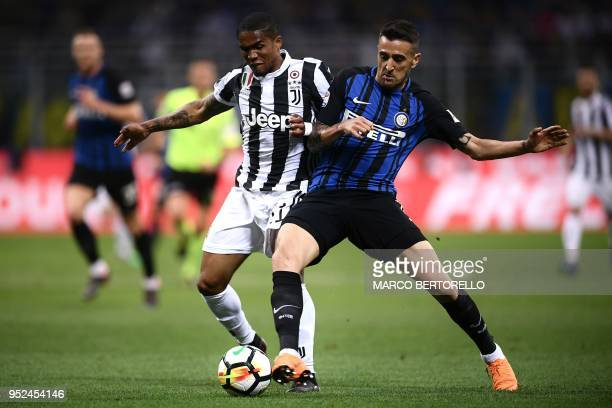 Juventus' midfielder Douglas Costa from Brazil fights for the ball with Inter Milan's midfielder Matias Vecino from Uruguay during the Italian Serie...