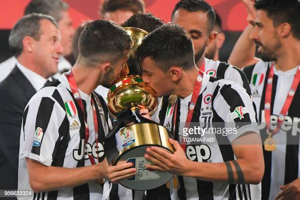 Juventus midfielder from Italy Miralem Pjanic and Juventus' forward from Argentina Paulo Dybala kiss the trophy after winning the Italian Tim Cup...