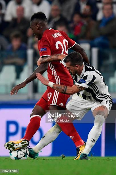 Juventus' midfielder from Italy Stefano Sturaro fights for the ball with Olympiacos' Nigerian Defender Emmanuel Emenike during the UEFA Champion's...