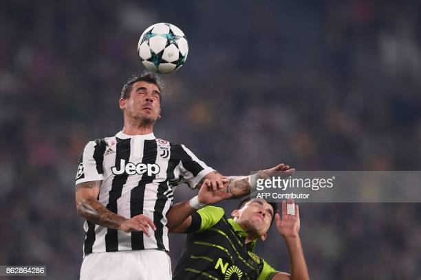 Juventus' midfielder from Italy Stefano Sturaro fights for the ball with Sporting's Argentinian forward Marcos Acuna during the UEFA Champions League...