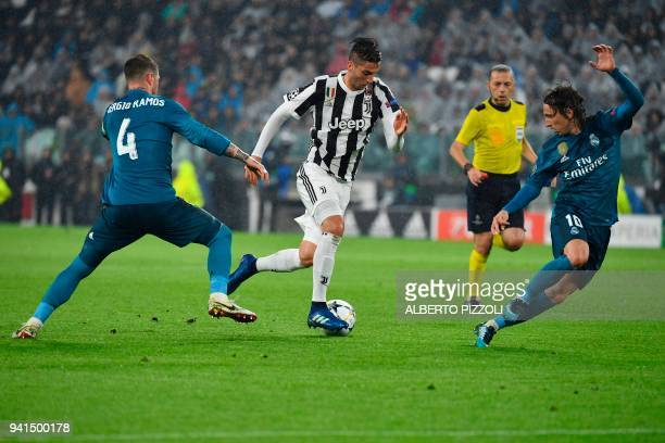 Juventus' midfielder from Uruguay Rodrigo Bentancur fights for the ball with Real Madrid's Spanish defender Sergio Ramos and Real Madrid's Croatian...
