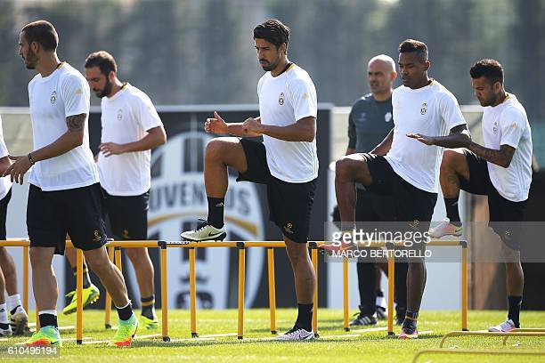 Juventus' midfielder Sami Khedira from Germany and Juventus' defender Alex Sandro from Brazil takes part in a training session on the eve of the UEFA...