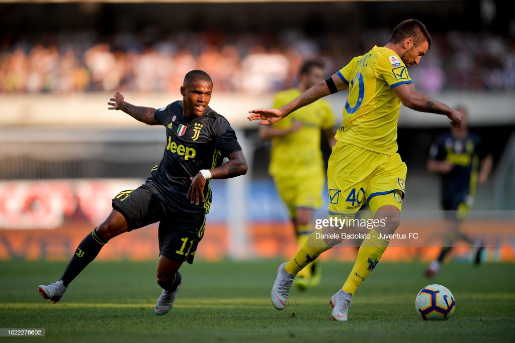 Juventus player Douglas Costa in action during the serie A match between Chievo Verona and Juventus at Stadio Marc'Antonio Bentegodi on August 18, 2018 in Verona, Italy.