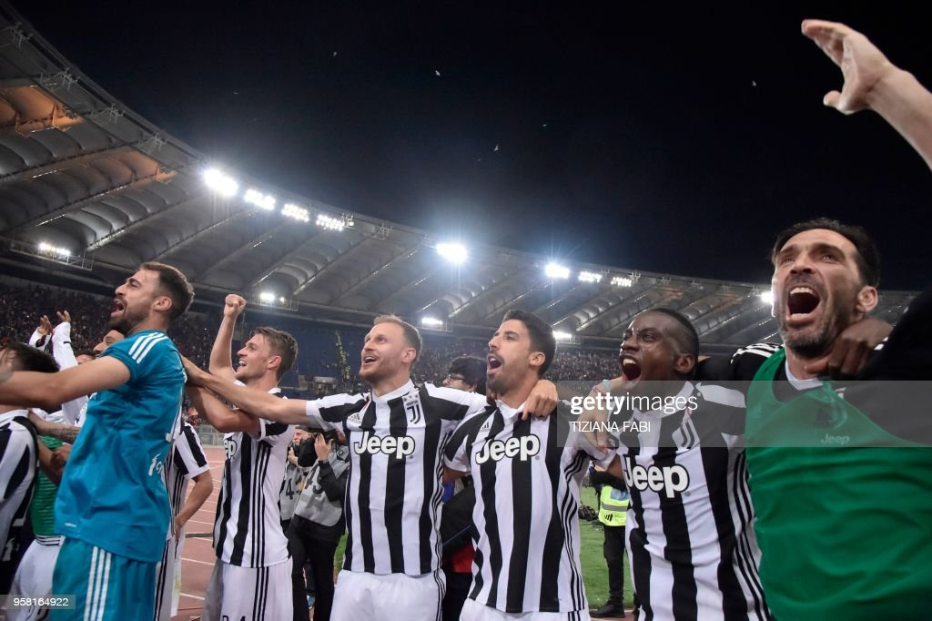 TOPSHOT - Juventus players celebrate at the end of the Italian Serie A football match AS Roma vs Juventus at the Olympic stadium on May 13, 2018 in Rome. Juventus won a seventh straight Serie A title on Sunday after a goalless draw against ten-man Roma at the Stadio Olimpico. - The Turin giants become the first team to complete the league and Cup double for four consecutive seasons. It is the 34th Scudetto in Juventus's history.
