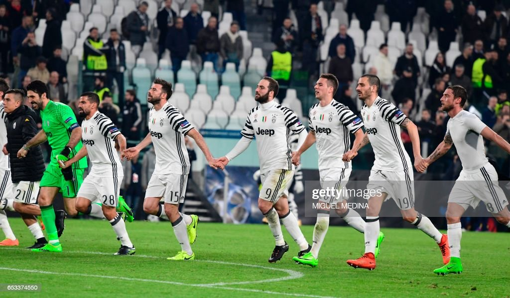 Juventus players celebrate with supporters after winning the UEFA Champions League football match Juventus vs FC Porto on March 14, 2017 at the Juventus stadium in Turin. / AFP PHOTO / Miguel MEDINA