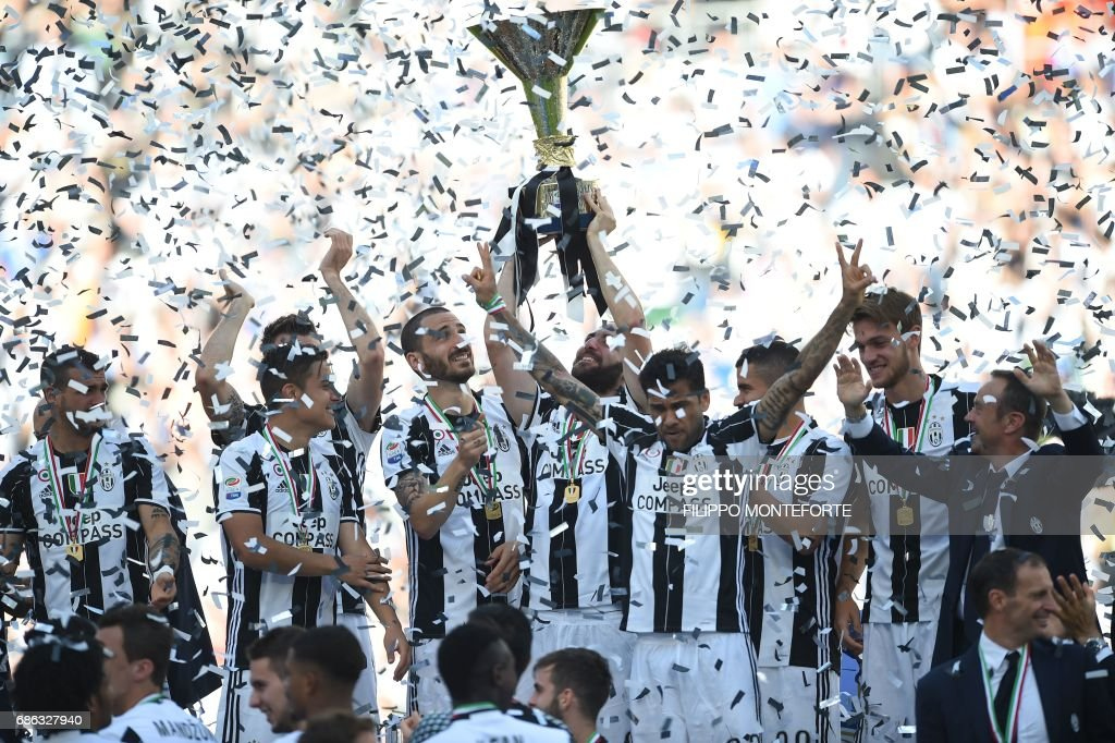 Juventus' players celebrate with the trophy after winning the Italian Serie A football match Juventus vs Crotone and the 'Scudetto' at the Juventus Stadium in Turin on May 21, 2017. First-half goals from Mario Mandzukic and Paulo Dybala, and a late header from Alex Sandro sealed a 3-0 win over Crotone to hand Juventus a record sixth consecutive Serie A title today. / AFP PHOTO / Filippo MONTEFORTE