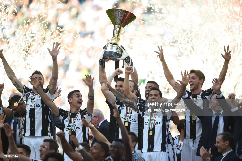 TOPSHOT - Juventus' players celebrate with the trophy after winning the Italian Serie A football match Juventus vs Crotone and the 'Scudetto' at the Juventus Stadium in Turin on May 21, 2017. First-half goals from Mario Mandzukic and Paulo Dybala, and a late header from Alex Sandro sealed a 3-0 win over Crotone to hand Juventus a record sixth consecutive Serie A title today. / AFP PHOTO / Filippo MONTEFORTE