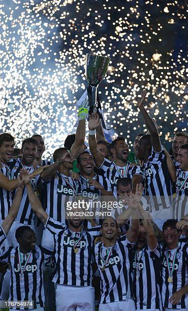 Juventus players celebrate with the trophy at the end of the Italian Supercup football match at the Olympic stadium in Rome on August 18 2013...