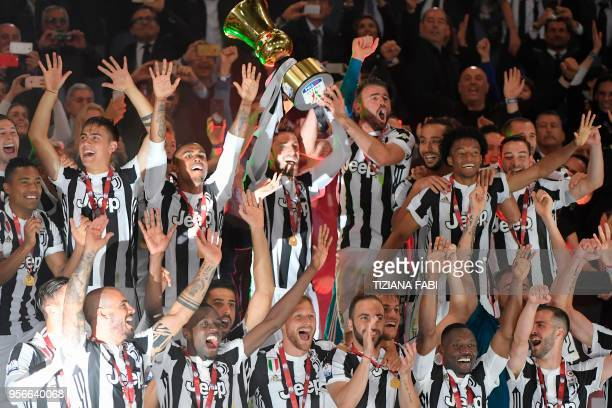Juventus' players celebrate with the trophy at the end of the Italian Tim Cup final Juventus vs AC Milan at the Olympic stadium on May 9, 2018 in...