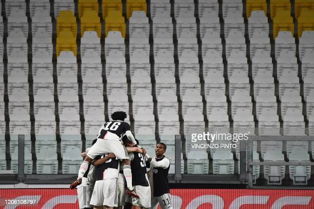 Juventus players celebrates after scoring their opener in an empty stadium due to the novel coronavirus during the Italian Serie A football match...