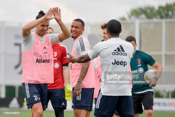 Juventus players Cristiano Ronaldo, Danilo and Douglas Costa joke during a training session at JTC on June 16, 2020 in Turin, Italy.
