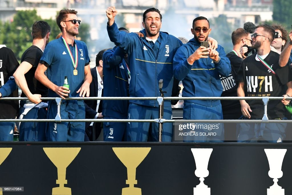 Juventus' players Daniele Rugani (L), goalkeeper Gianluigi Buffon (C) and defender Medhi Benatia parade with teammates aboard an open-top bus to celebrate the 'scudetto' with supporters in Turin after the Italian Serie A last football match of the season, on May 19, 2018. Juventus won their 34th Serie A title and seventh in succession.