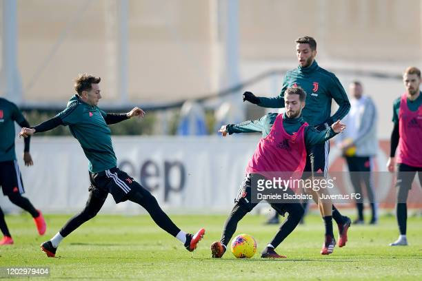Juventus players Federico Bernardeschi competes for the ball with Miralem Pjanic during a training session at JTC on January 30 2020 in Turin Italy