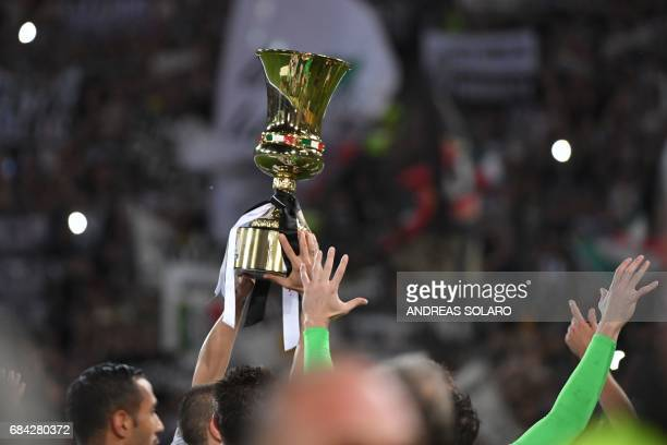Juventus' players hold the trophy after winning the Italian Tim Cup final on May 17 2017 at the Olympic stadium in Rome Dani Alves and Leonardo...