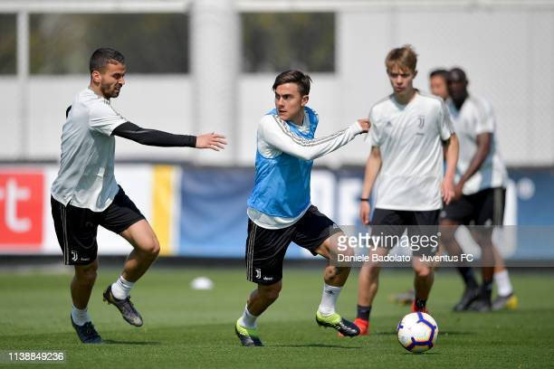 Juventus players Leonardo Spinazzola and Paulo Dybala compete for the ball during a training session at JTC on March 28 2019 in Turin Italy