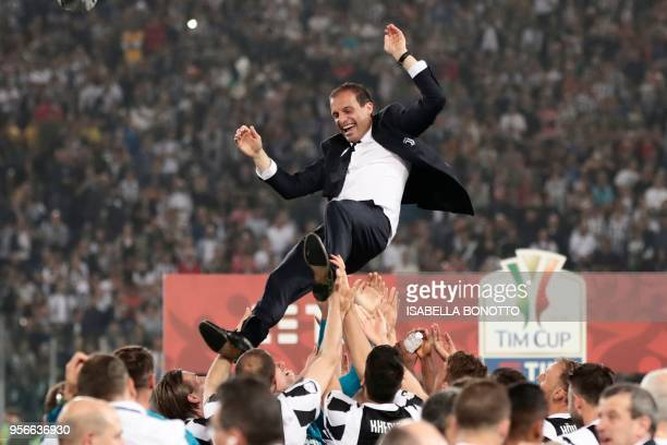 TOPSHOT Juventus players lift Juventus' coach from Italy Massimiliano Allegri after winning the Italian Tim Cup final Juventus vs AC Milan at the...
