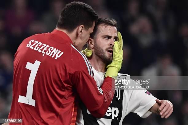 Juventus' Polish goalkeeper Wojciech Szczesny congratulates Juventus' Bosnian midfielder Miralem Pjanic after he saved a ball in the penalty area...