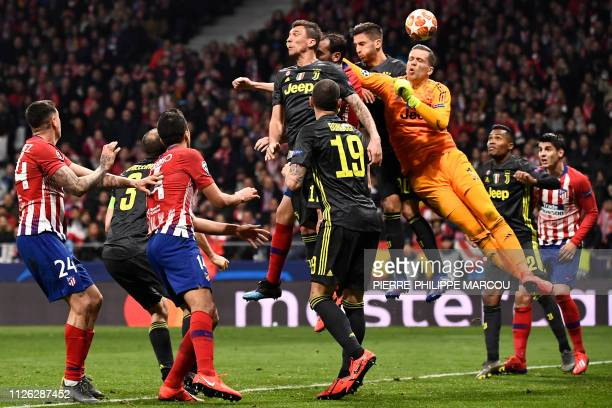 Juventus' Polish goalkeeper Wojciech Szczesny jumps to clear the ball during the UEFA Champions League round of 16 first leg football match between...