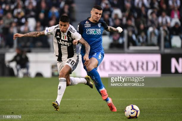 Juventus' Portuguese defender Joao Cancelo and Empoli's Italian midfielder Simone Canestrelli go for the ball during the Italian Serie A football...