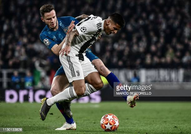 Juventus' Portuguese defender Joao Cancelo holds off Atletico Madrid's Spanish midfielder Saul Niguez during the UEFA Champions League round of 16...